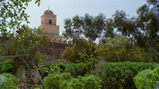 vídeos de stock e filmes b-roll de ms, great mosque behind trees, kairouan, tunisia - por volta do século 7 dc