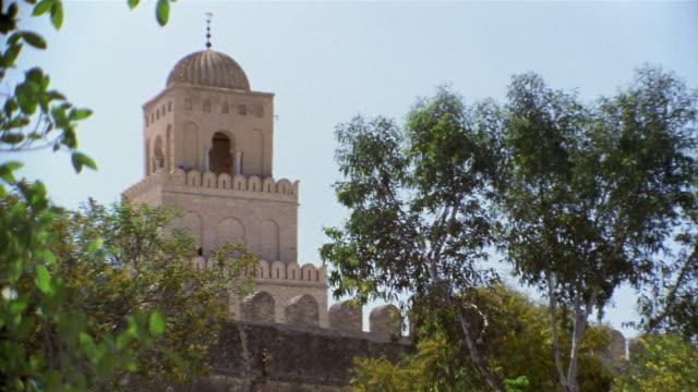 vídeos de stock e filmes b-roll de cu, great mosque behind trees, kairouan, tunisia - por volta do século 7 dc