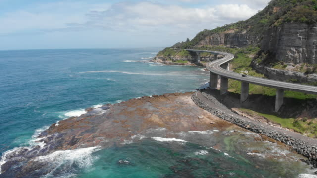 great ocean road drive along the stunning sea cliff bridge hugging the coast south of sydney - new south wales stock videos & royalty-free footage
