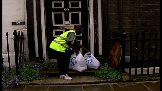 great ormond street hospital warn of fake charity workers clothes aid worker picking up bag from outside house motorcyclist out onto street to... - fake hospital stock videos & royalty-free footage
