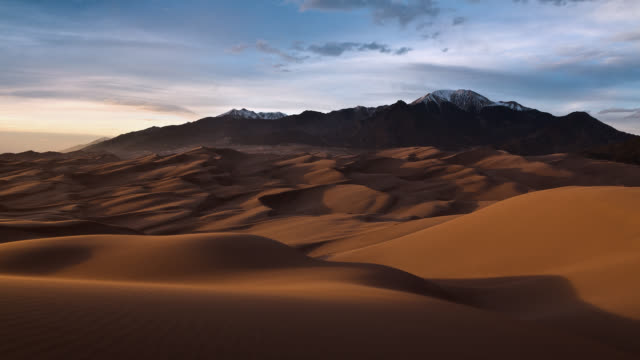 vídeos de stock e filmes b-roll de t/l great sand dunes national park with view of sangre de cristo mountains at sunset / great sand dunes national park and preserve, colorado, usa - cordilheira montanha