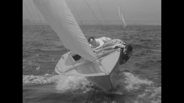 ms great shot of starclass yacht racing toward camera as its two man crew hang onto the side prevent capsizing another boat in background / ms boat... - capsizing stock videos and b-roll footage