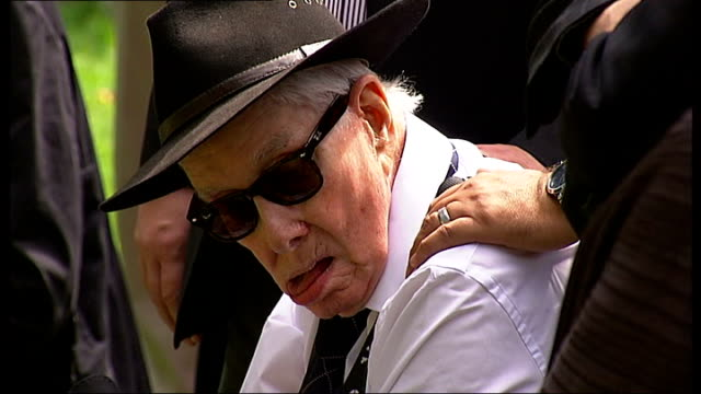 great train robber ronnie biggs death; t08081353 / tx london: highgate cemetery: ronnie biggs in wheelchair at funeral of bruce reynolds - highgate stock videos & royalty-free footage