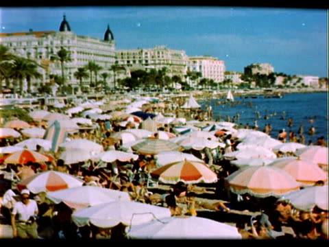 great very crowded beach on shore of cote d' azur french riviera france / beach umbrellas tourists sunbathers and sunworshippers waves rolling slowly... - region provence alpes côte d'azur stock-videos und b-roll-filmmaterial