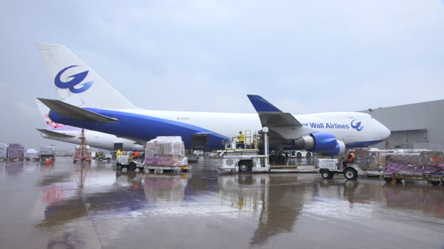 ZO Great Wall Airlines cargo plane (Boeing 747-400F)  on rain-slicked tarmac with trucks moving cargo in foreground/DFW International Airport, Dallas-Fort Worth, Texas, USA