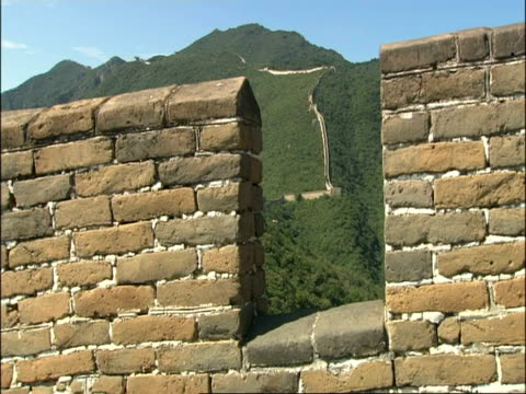 great wall of china snaking up hill, shot through battlements, mutianyu, china - mutianyu stock videos & royalty-free footage