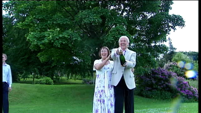greater manchester bolton ext brian and joan caswell opening bottle of champagne and posing with cheque for nearly 25 million pounds - bolton greater manchester stock videos and b-roll footage
