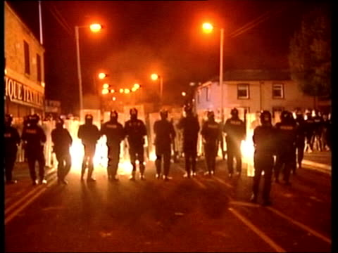 Oldham BV Line of riot police as rioters throw petrol bombs towards them