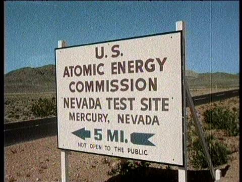 / greatest headlines of the century / no audio / doom town atomic blast test / at the u s atomic energy commission nevada test site / men busy... - 原子爆弾点の映像素材/bロール