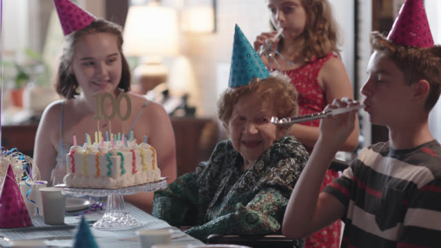 vidéos et rushes de great-grandchildren all kiss their great-grandmother after blowing out the candles on her birthday cake during her 100th birthday party - anniversaire