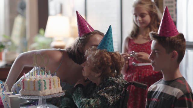 great-grandchildren all kiss their great-grandmother one by one after blowing out the candles on her birthday cake during her 100th birthday party - birthday gift stock videos & royalty-free footage