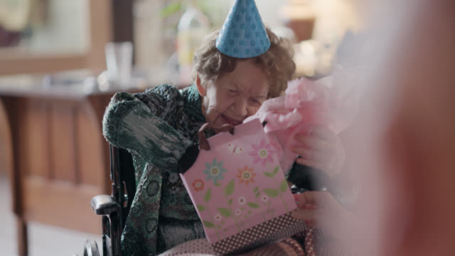 vídeos y material grabado en eventos de stock de great-grandchildren watch their great-grandmother open a birthday present inside a gift bag during her 100th birthday party - huésped