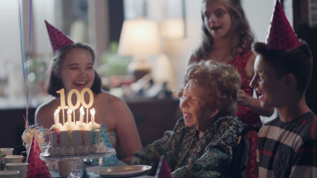 vídeos de stock, filmes e b-roll de great-grandmother and her great-grandchildren sing happy birthday while her candles burn on her birthday cake during her 100th birthday party - dividir