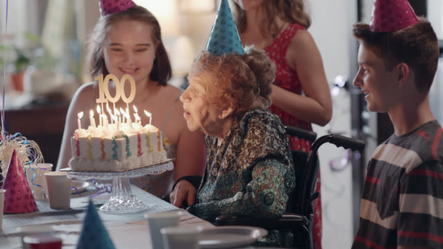 great-grandmother and her great-grandson blow out the candles on her birthday cake during her 100th birthday party - compleanno video stock e b–roll