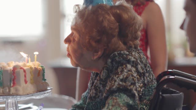 great-grandmother blows out the candles on a birthday cake while celebrating her 100th birthday party with her family - compleanno video stock e b–roll