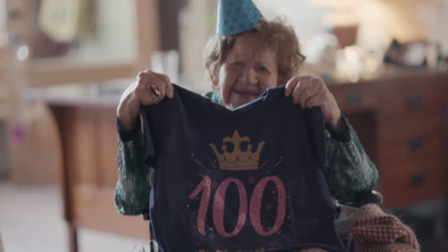 """great-grandmother holds up a slogan t-shirt with the saying """"100 & fabulous"""" she received as a gift for her 100th birthday - paper bag stock videos & royalty-free footage"""