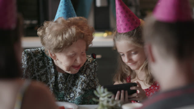 great-grandmother looks at a smart phone with her great granddaughter while celebrating together at her 100th birthday party - wheelchair stock videos & royalty-free footage