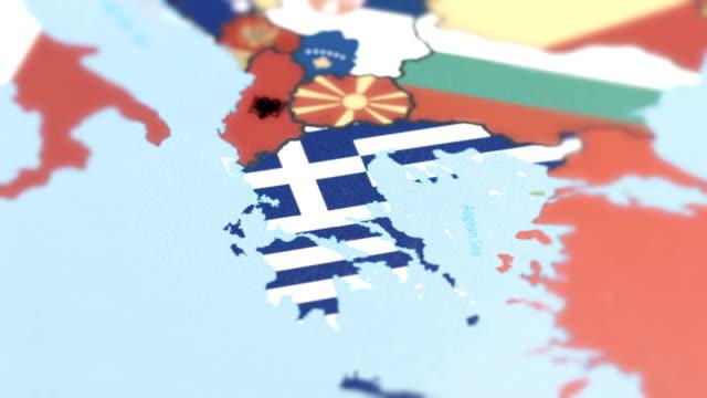griechenland grenzt nationalflagge auf weltkarte - griechische flagge stock-videos und b-roll-filmmaterial