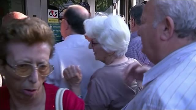 Greece secure bail out deal with Eurozone leaders Athens EXT Various shots of people queuing up for cash machine Poster depicting the government as a...