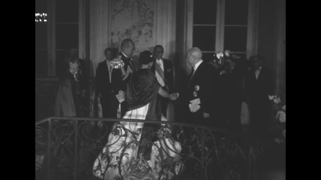 Greece's King Paul and wife Queen Frederica walk up stairway in Augustusburg Palace in Bruhl West Germany / CU chandelier / Frederica and Paul shake...