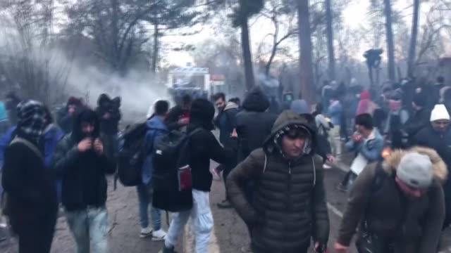 stockvideo's en b-roll-footage met greek border guards use tear gas to disperse hundreds of irregular migrants wait at the turkeys pazarkule border crossing with greece's kastanies in... - vluchteling ontheemden