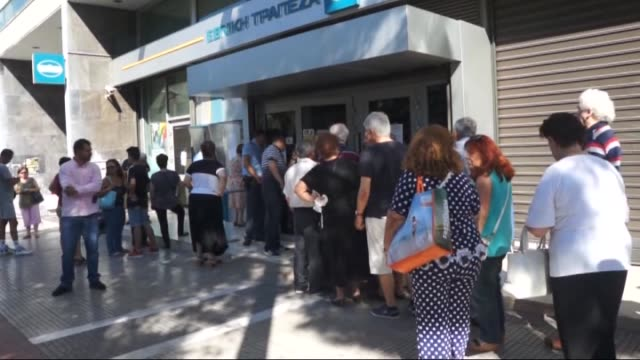 greek citizens wait outside the main gate of the national bank of greece to withdraw a cash in central athens, greece on july 9, 2015. the government... - 2015点の映像素材/bロール