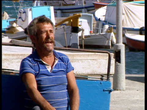 greek fisherman standing by boat thrusts both hands out-palm first as part of hand gesture insult greece - human limb stock videos & royalty-free footage