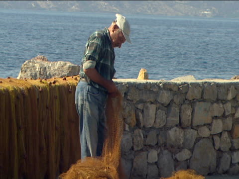 vídeos de stock e filmes b-roll de greek fisherman untangles net on harbor wall aegean sea in background - rede de pesca comercial