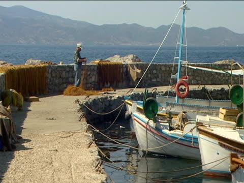 vídeos de stock e filmes b-roll de greek fisherman untangles net on harbor wall beside fishing boats - rede de pesca comercial