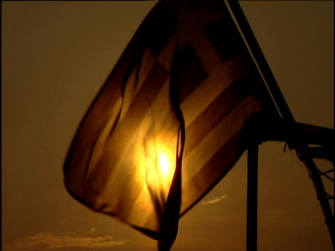 greek flag blowing in the breeze with sun behind. sepia filter applied. - greek flag stock videos & royalty-free footage