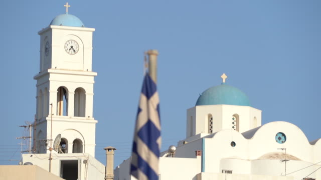 greek flag flaps in wind in front of white and blue architecture - greek flag stock videos & royalty-free footage