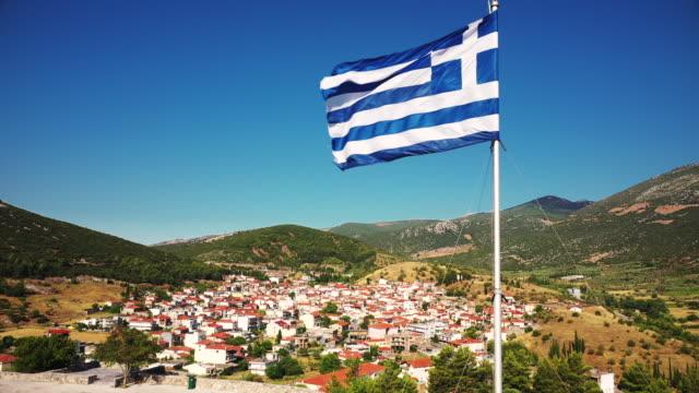 greek flag over mountain village of distomo - ギリシャ国旗点の映像素材/bロール