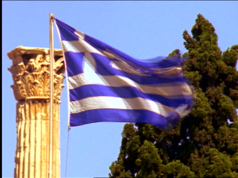 greek flag waving in front of columns at temple of zeus under blue sky / athens, greece - ギリシャ国旗点の映像素材/bロール