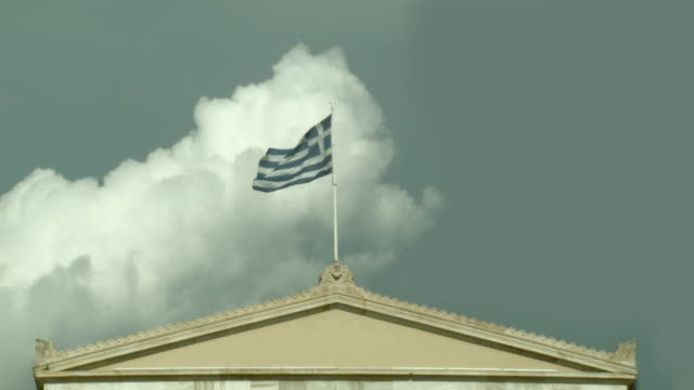 greek flag waving over the parliament from real-time to slow-motion with blue sky and a white cloud at the background - griechenland stock-videos und b-roll-filmmaterial