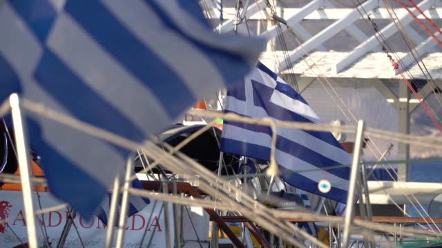 griechische fahnen flattern im wind aus segelboote im griechischen hafen - griechische flagge stock-videos und b-roll-filmmaterial