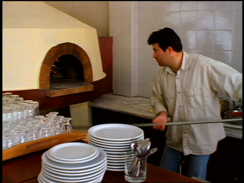 greek man taking pizzas out of brick oven with pole in restaurant / greece - hearth oven stock videos & royalty-free footage
