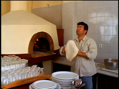 greek man tossing pizza dough near brick oven in restaurant / greece - unhealthy eating stock videos & royalty-free footage