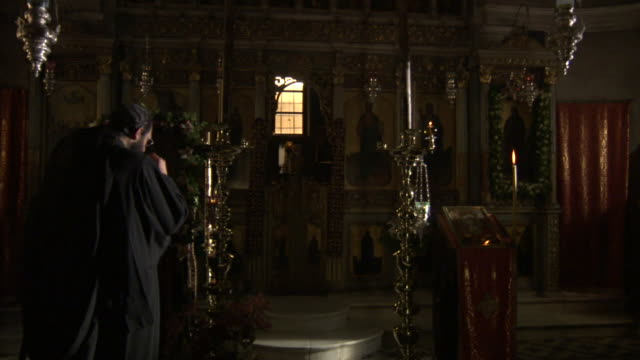 a greek orthodox monk performs rituals in front of a podium and candles in a church. - clergy stock videos & royalty-free footage