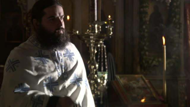 vidéos et rushes de a greek orthodox priest shakes incense during a ritual in a church. - prêtre