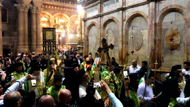 greek orthodox priests lead a procession through the church of the holy sepulchre in the old city on april 1 2018 in jerusalem israel thousands of... - israele video stock e b–roll