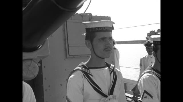 vidéos et rushes de greek sailors stand at attention with bayoneted rifles/ vs faces of personnel with officers standing behind / greek naval ensign flutters in the wind... - baïonnette