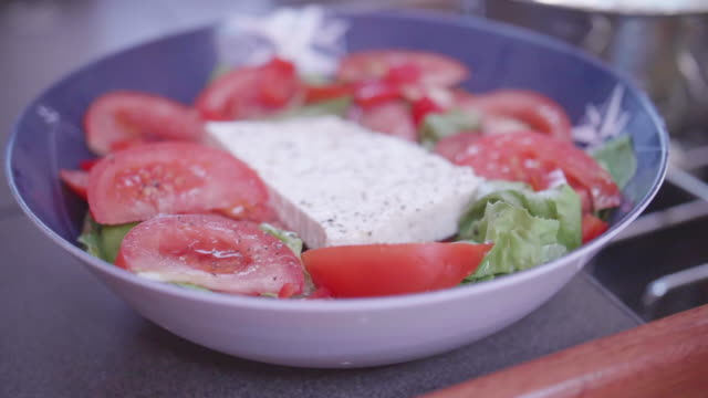 a greek salad with feta cheese for lunch on a sailboat boat. - käse stock-videos und b-roll-filmmaterial