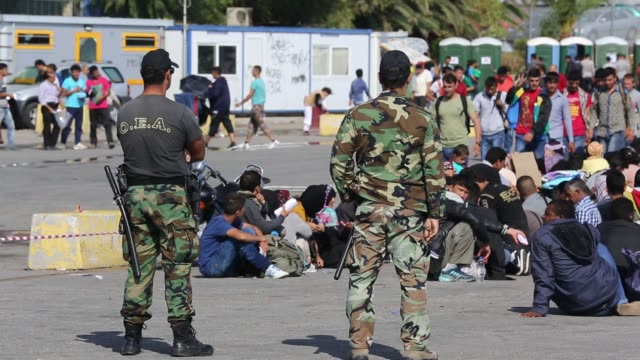 greek soldiers guard syrian migrants fleeing the war and escaping to europe, who have landed on the greek island of lesvos on the north coast at efthalou. up to 4,000 migrants a day are landing on the island and overwhelming the authorities. they are trafi - illegaler einwanderer stock-videos und b-roll-filmmaterial