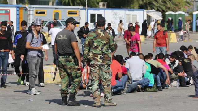 vídeos y material grabado en eventos de stock de greek soldiers guard syrian migrants fleeing the war and escaping to europe, who have landed on the greek island of lesvos on the north coast at efthalou. up to 4,000 migrants a day are landing on the island and overwhelming the authorities. they are trafi - guerra civil