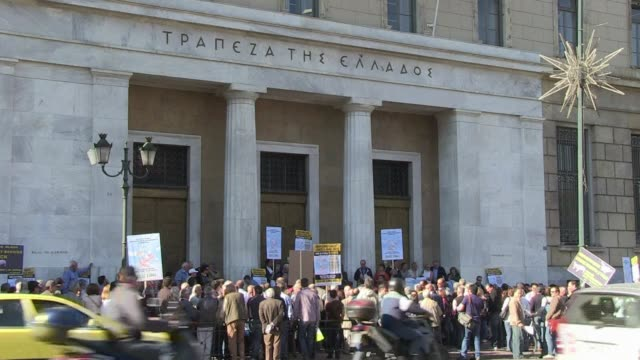 greek state bond holders protest outside the bank of greece saying their shares have lost their value and that the state isn't compensating them... - grecia stato video stock e b–roll