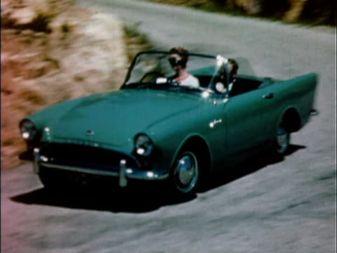 1959 ws pan green 1959 sunbeam alpine driving along winding road / united kingdom - 1950 1959 個影片檔及 b 捲影像