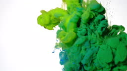 Green and blue watercolor ink mixed in water on a white background. Slow motion of colored acrylic paints in water.