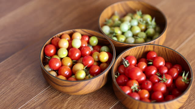 green and red cherry tomatoes in three bowls on wooden table - cherry tomato stock videos & royalty-free footage
