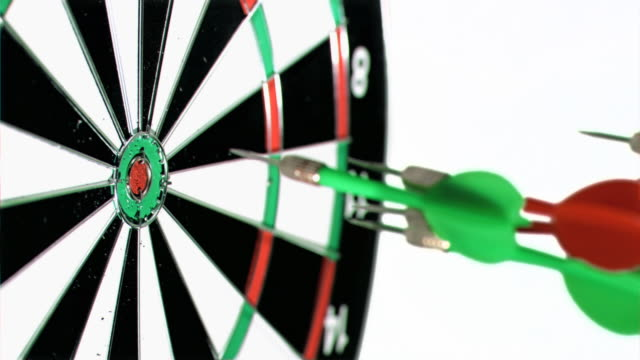 green and red darts in super slow motion thrown at a dart board - dart board stock videos & royalty-free footage