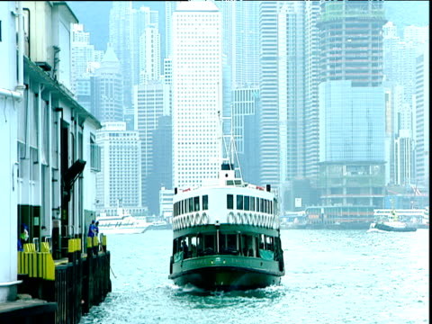 green and white passenger ferry comes into dock skyscrapers in background hong kong - ferry stock videos & royalty-free footage
